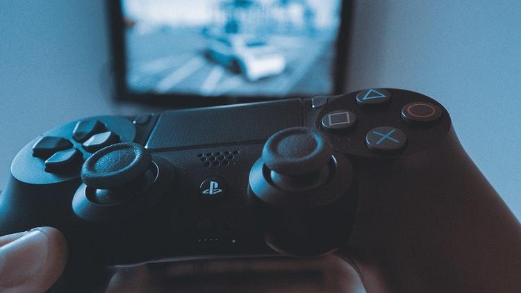 Playstation 4 kontroll med tv i bakgrunden